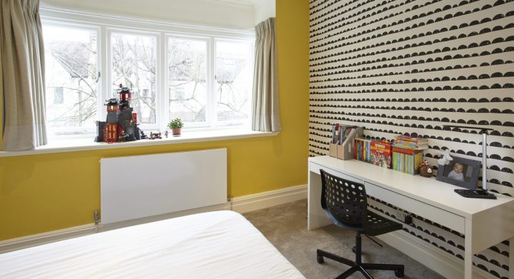Yellow wal and textured wallpaper in bedroom