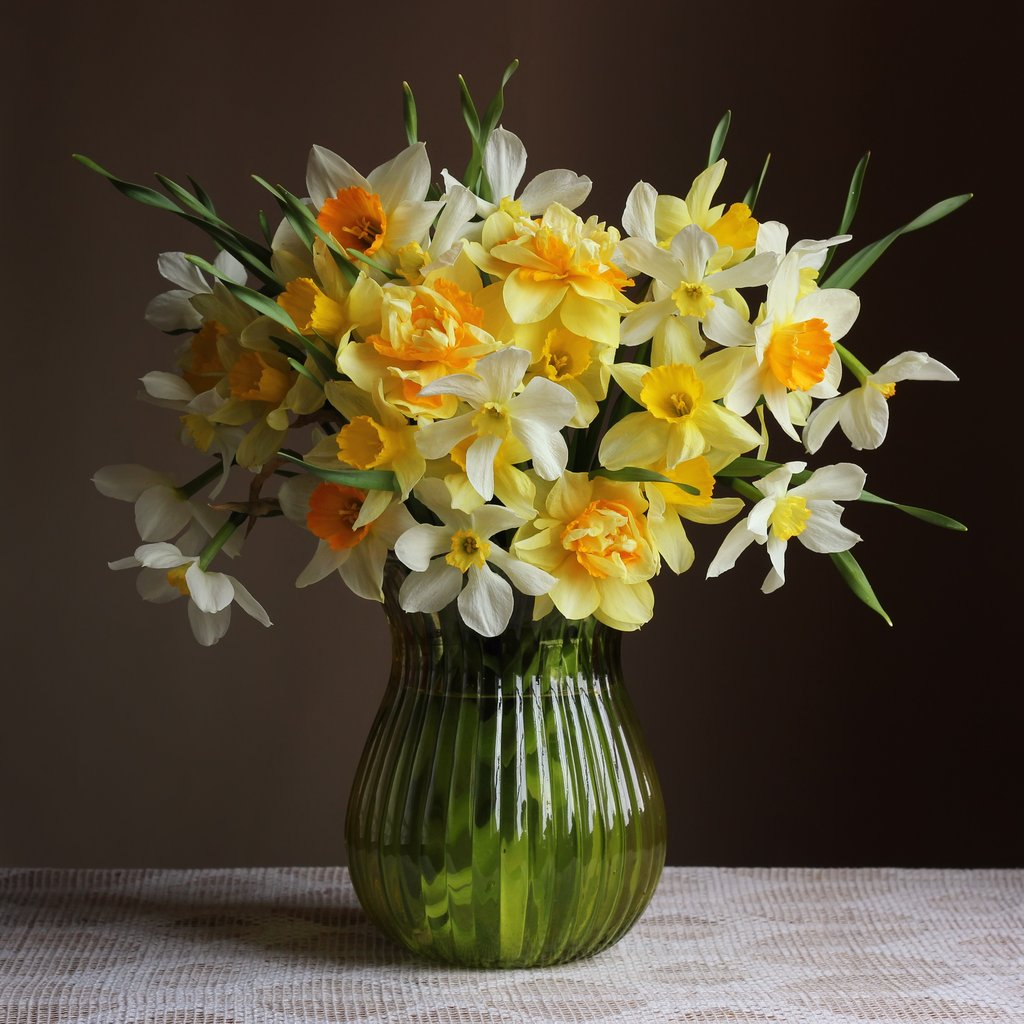 Bouquet of yellow daffodils in a glass vase on a dark background.