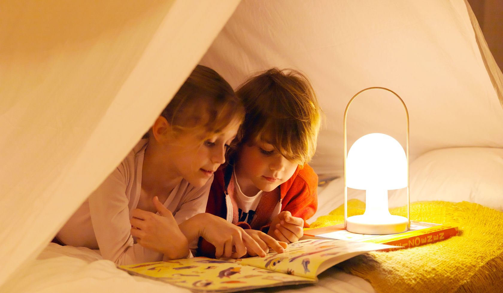Kids reading in a tent with a portable light
