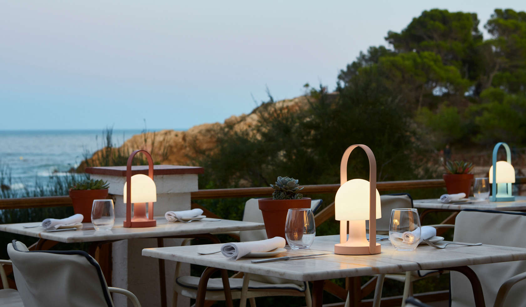 Portable lights on outdoor tables with a view of the sea