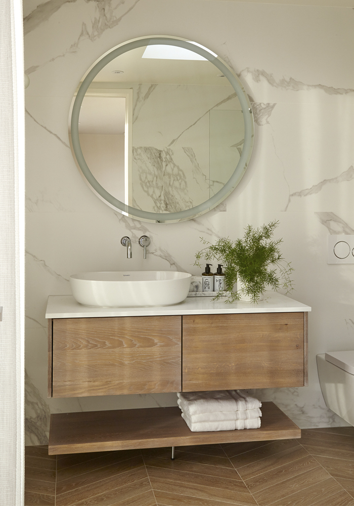 Round mirror above bathroom basin