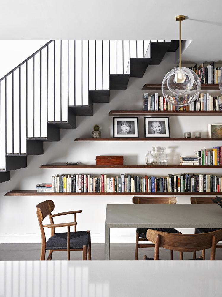Cantilevered bookshelves under stairs