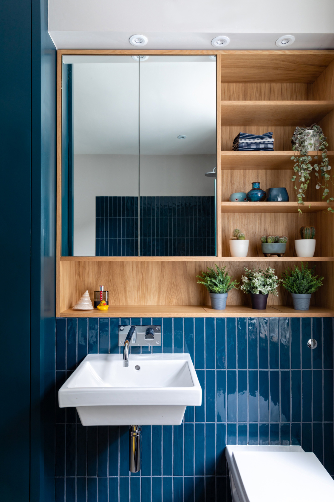 Blue tiles and wooden shelves in chelsea town house bathroom