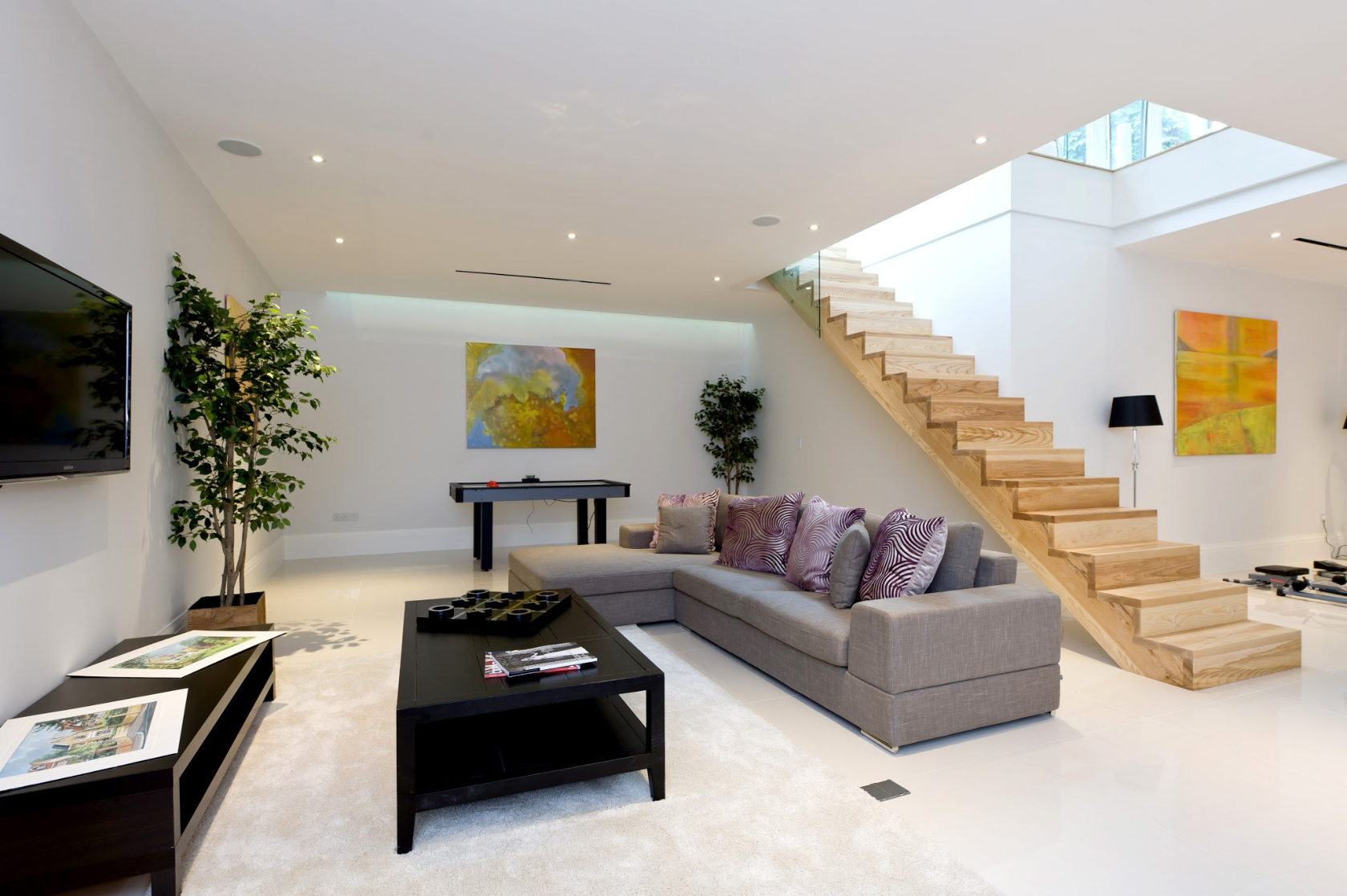 A basement family room with a TV lounge, gym area and table-football under a new-build house in SW20