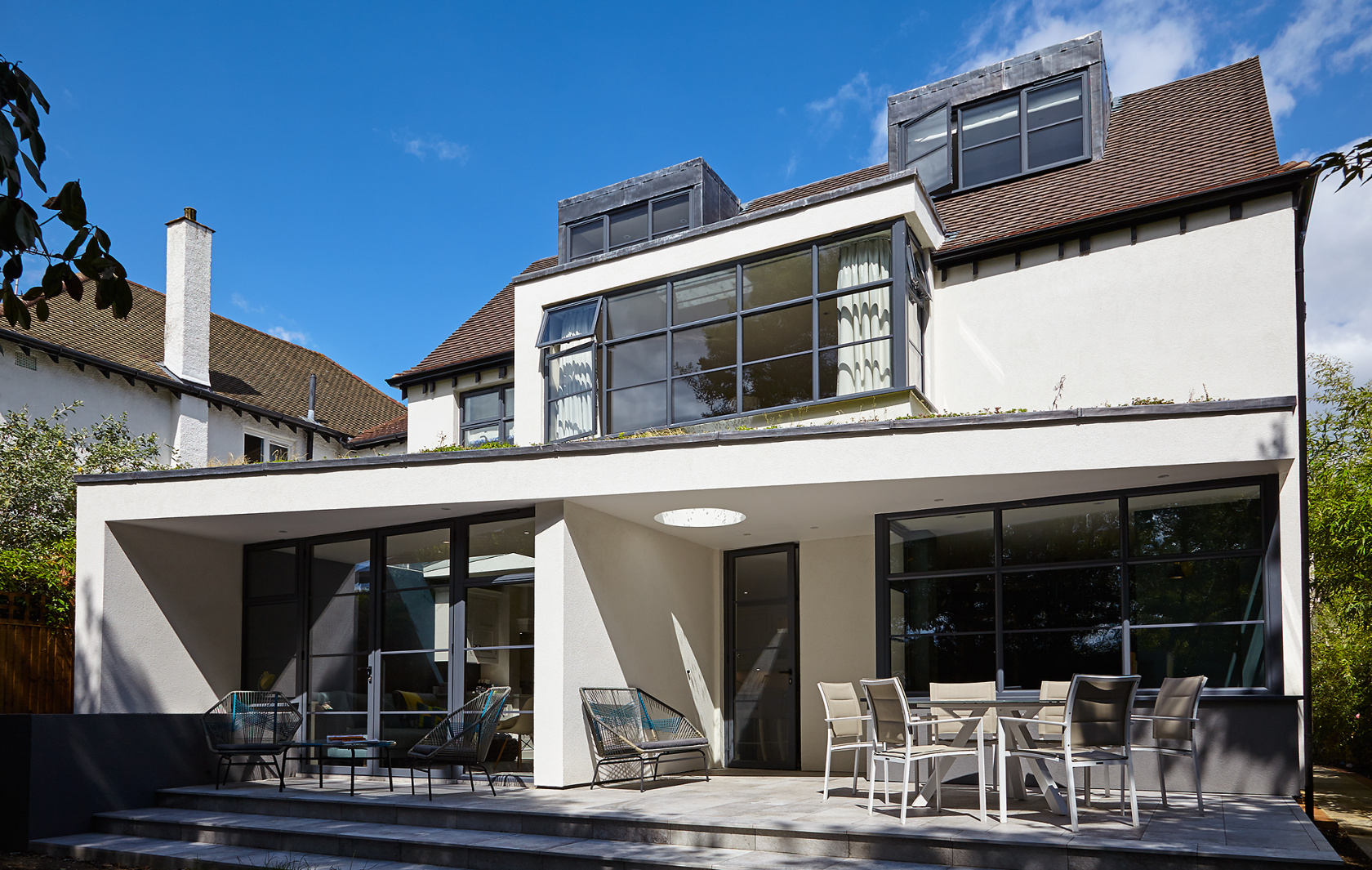 House refurbishment and extensions in SW20, ground floor spaces transition onto the garden terrace.