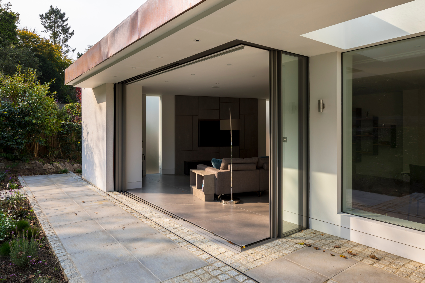 Pocket sliding floor-to-ceiling doors to a family room opening onto the garden