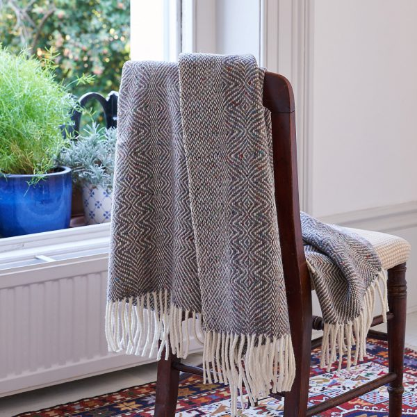 Donegal Twill Throw in Fossil by Craft Editions available at The Decorcafe lifestyle image showring throw draped over a chair