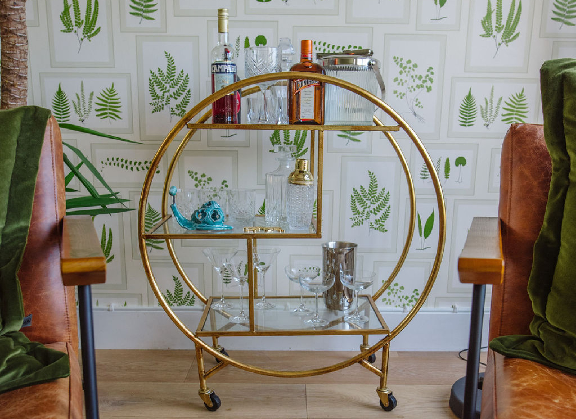 Biophilic design interior featuring gold bar cart drinks trolley and plant illustration wallpaper.